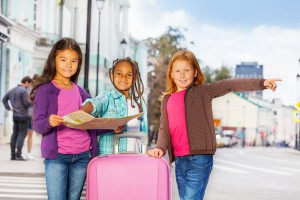 32962629 - beautiful girls stand with map and luggage in city