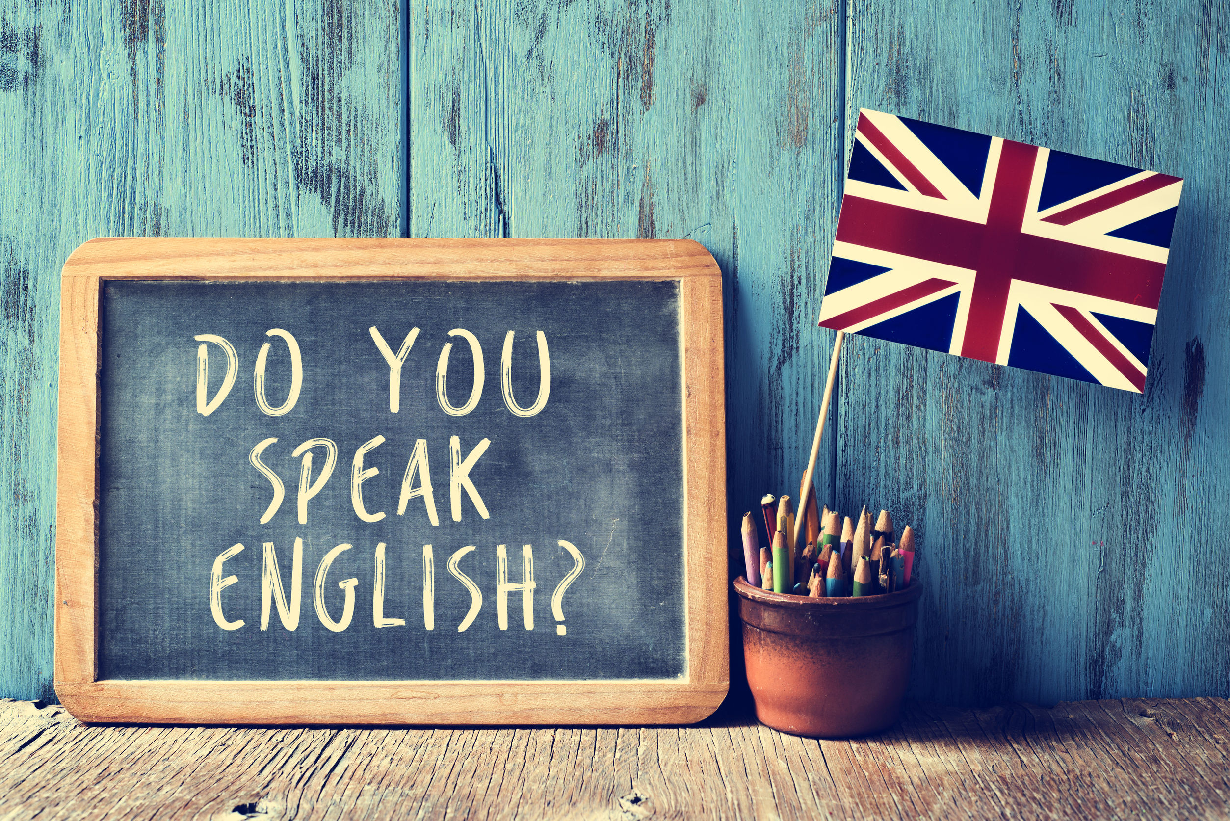 En un pizarra aparece Do you speak english y está junto a un recipiente con lapices y una bandera inglesa pequeña